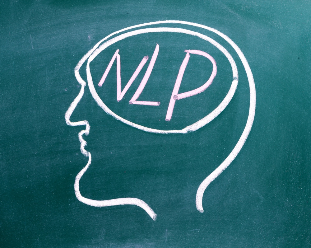 A picture of human skull with NLP the abbreviation for near-linguistic programming where the brain should be